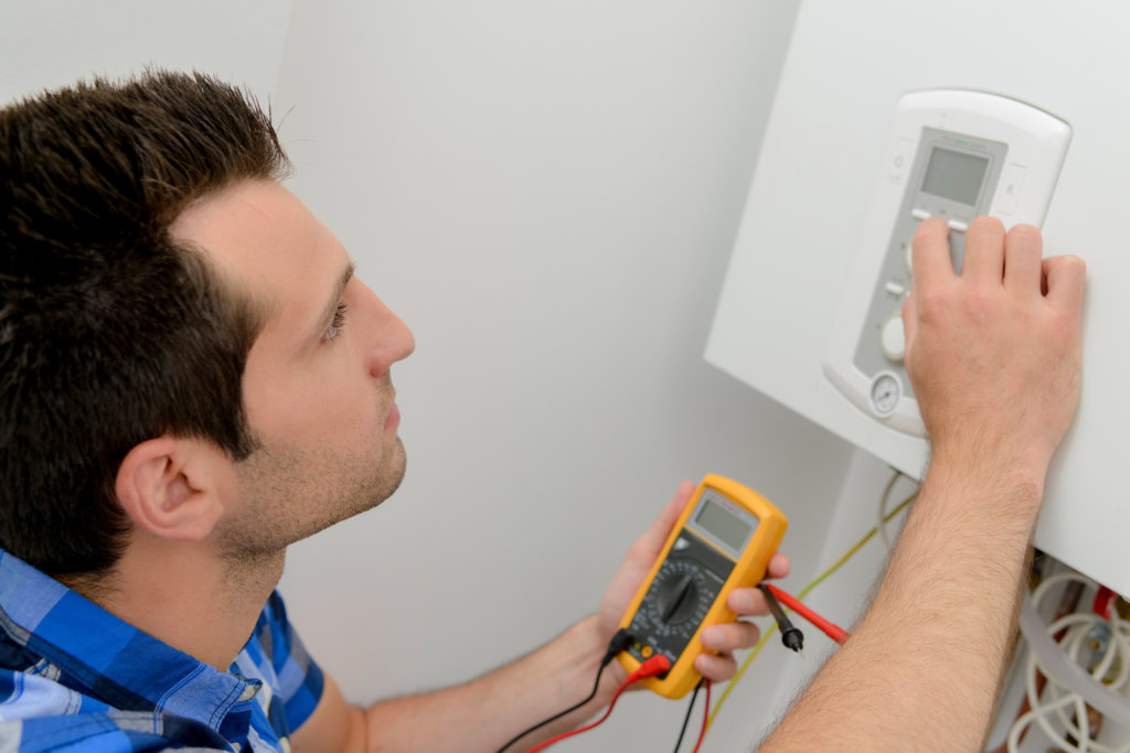 Técnico de manutenção analisa indicadores de um sistema de climatização