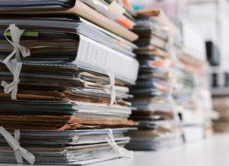 Papéis e documentos empilhados em uma mesa de escritório. Resultado de uma gestão de documentos ineficiente.
