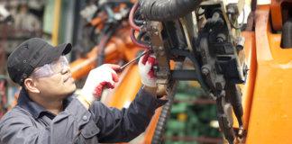 Técnico de manutenção efetuando análise e reparo em uma máquina industrial